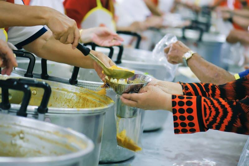 Alimento da parte dos voluntários aos pobres para aliviar a fome: Conceito da caridade fotos de stock