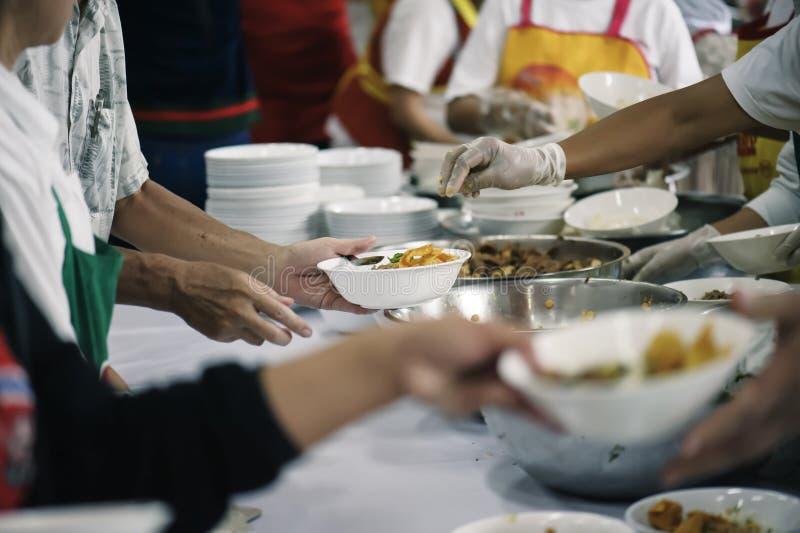 Alimento da parte dos voluntários aos pobres para aliviar a fome: Conceito da caridade foto de stock