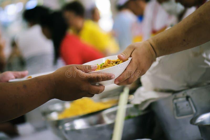 Alimento da parte dos voluntários aos pobres para aliviar a fome: Conceito da caridade fotografia de stock