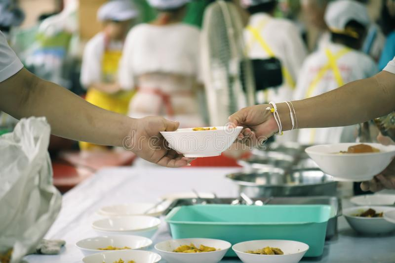 Alimento da parte dos voluntários aos pobres para aliviar a fome: Conceito da caridade foto de stock royalty free