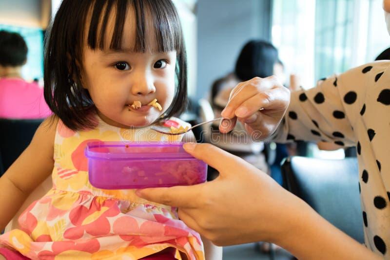 Alimento de alimentação da filha da criança da mãe asiática fotos de stock