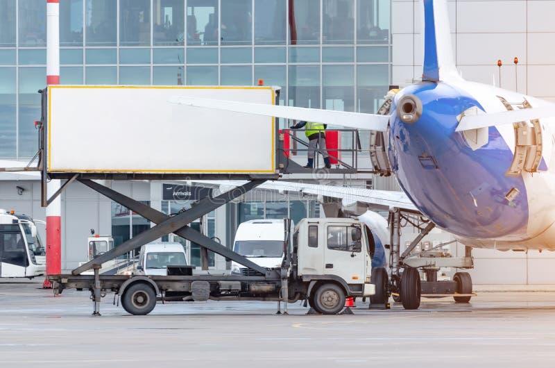Alimento de carregamento no plano para passageiros no terminal fotos de stock royalty free