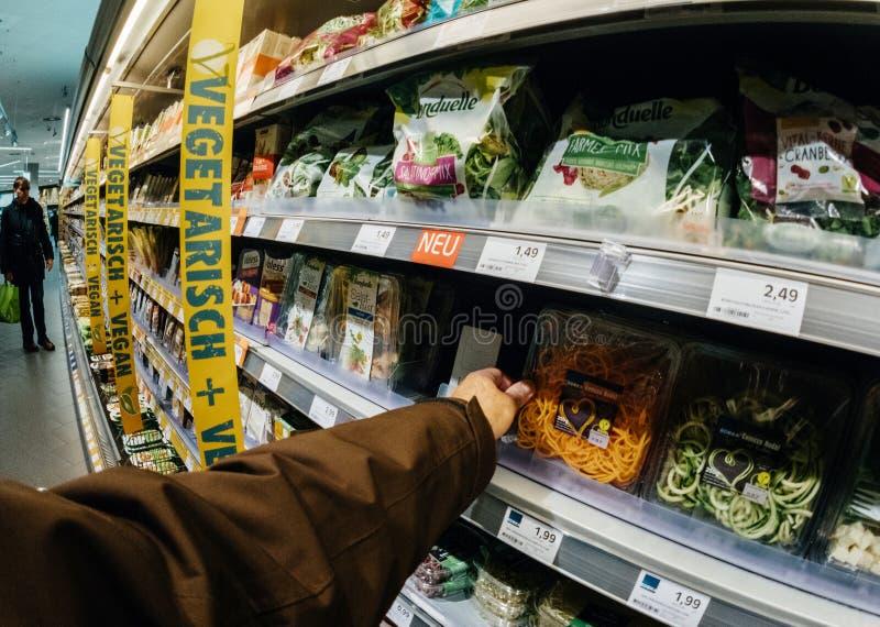 Alimento de compra do vegetariano do vegetariano do cliente masculino no supermakert fotografia de stock