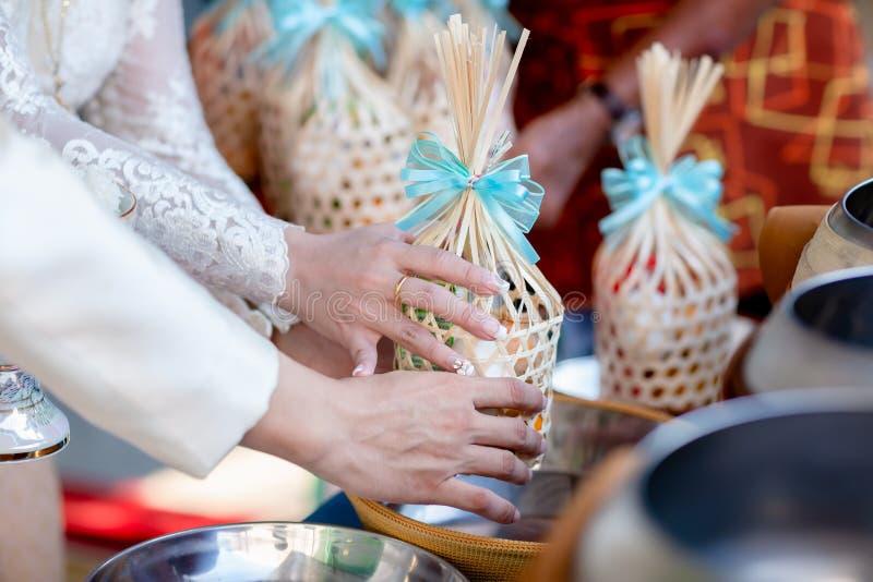 Alimento de la oferta al monje El novio da la comida de las limosnas a un monje budista en ceremonia que se casa tailandesa tradi foto de archivo libre de regalías