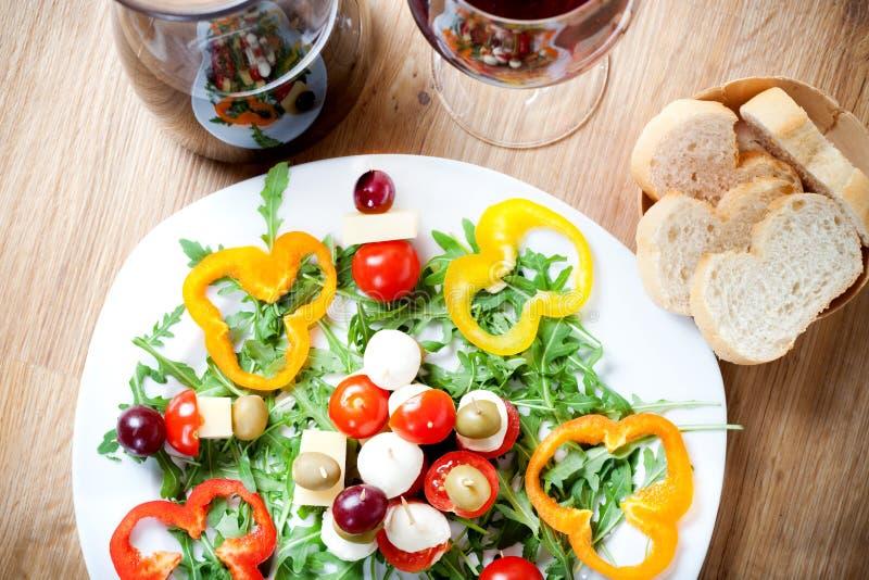 Alimento del cercatore con la mozzarella, l'insalata di razzo, l'uva e le olive, vite, pavimentazione di legno immagine stock libera da diritti