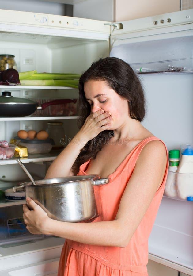 Alimento del fallo della tenuta della donna vicino al frigorifero fotografia stock libera da diritti