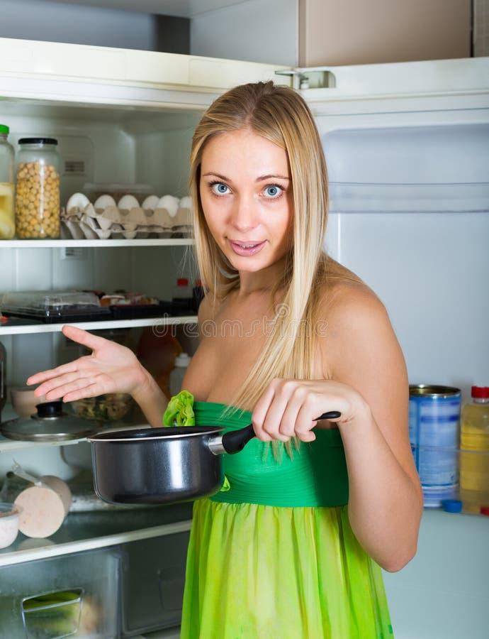 Alimento del fallo della tenuta della donna vicino al frigorifero immagini stock libere da diritti