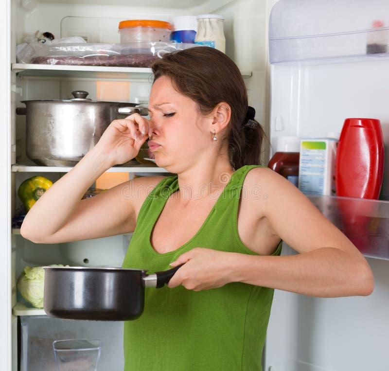 Alimento del fallo della tenuta della donna vicino al frigorifero immagine stock libera da diritti