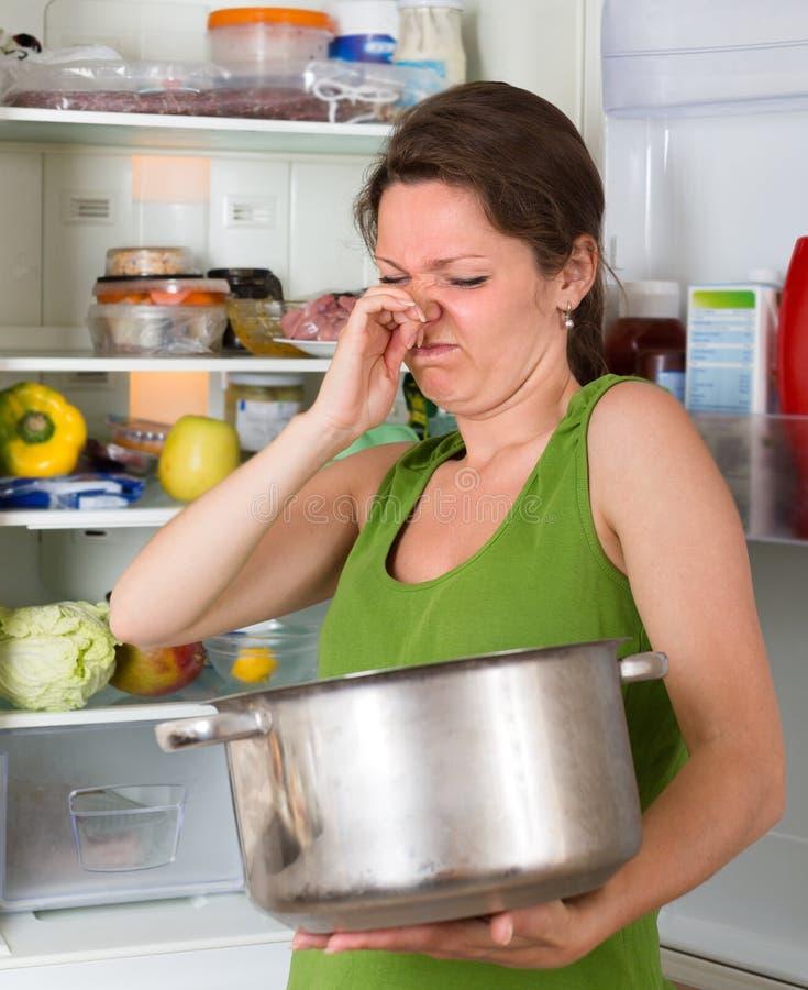 Alimento del fallo della tenuta della donna vicino al frigorifero fotografia stock