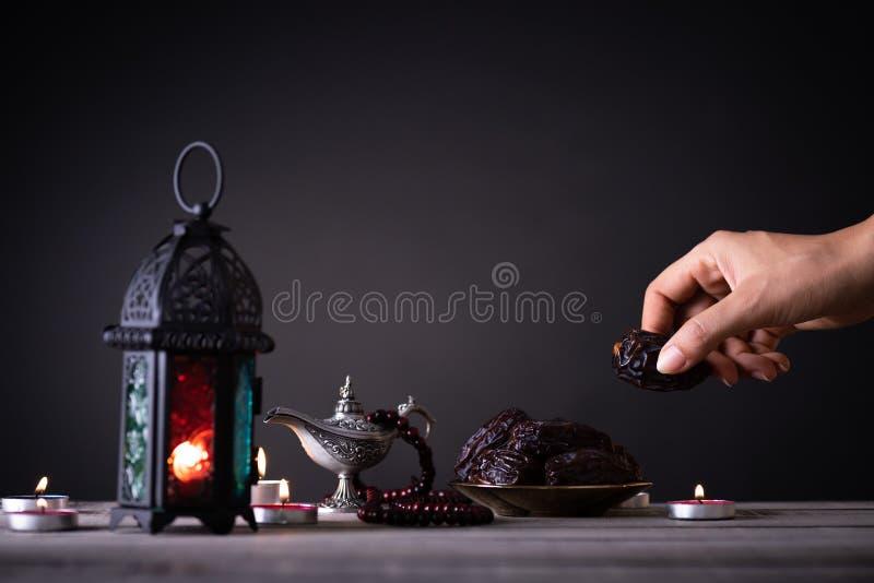 Alimento del Ramadan e concetto delle bevande La mano della donna raggiunge fuori ad un piatto con la data con Ramadan Lantern co fotografie stock