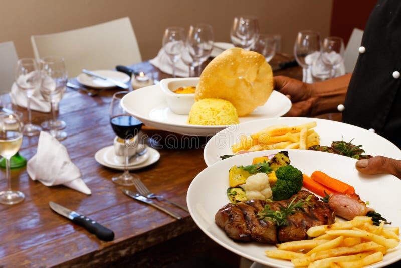 Alimento del servizio del cuoco unico del ristorante ad una tabella fotografia stock libera da diritti