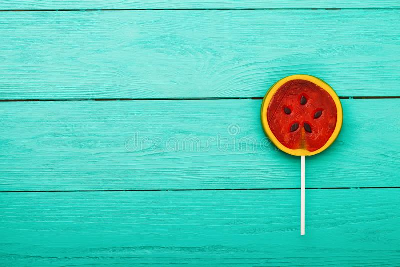 Alimento della caramella di estate dell'anguria su fondo di legno blu Vista superiore Derisione su Copi lo spazio Lollipop dolce fotografia stock libera da diritti