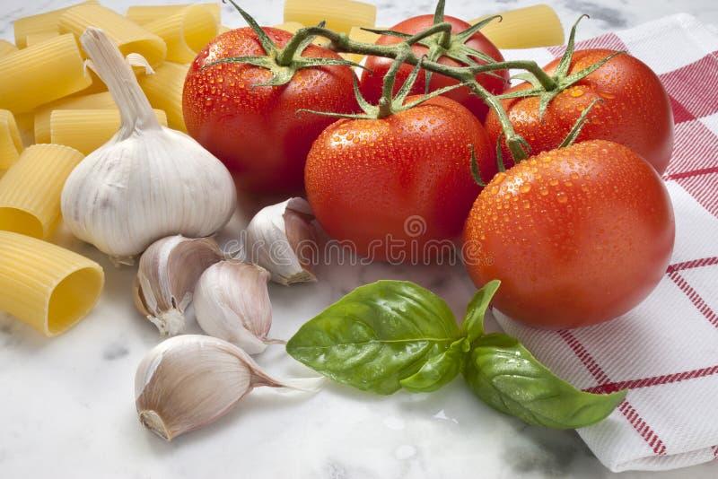 Alimento della pasta del basilico dell'aglio dei pomodori fotografia stock