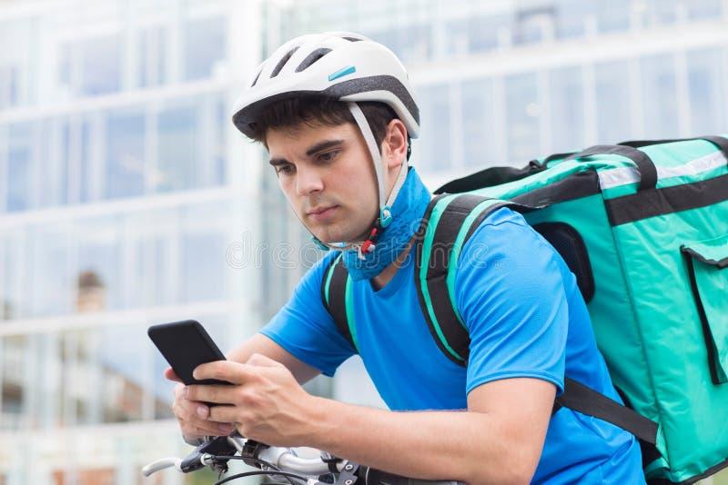 Alimento di On Bicycle Delivering del corriere in città facendo uso del telefono cellulare fotografia stock libera da diritti