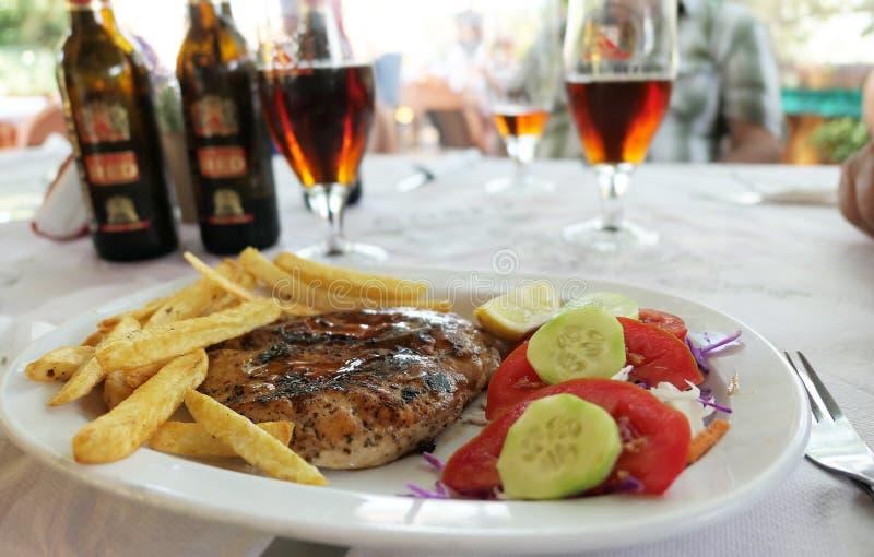 Alimento di Corfù di tradizione ad una locanda con il pollo, patate fritte e fotografia stock libera da diritti