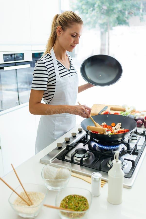 Alimento di cottura e mescolantesi della giovane donna in buona salute in padella nella cucina a casa immagini stock libere da diritti