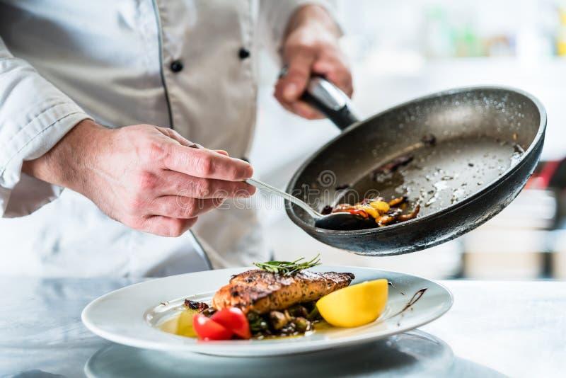 Alimento di rifinitura del cuoco unico nella sua cucina del ristorante fotografia stock