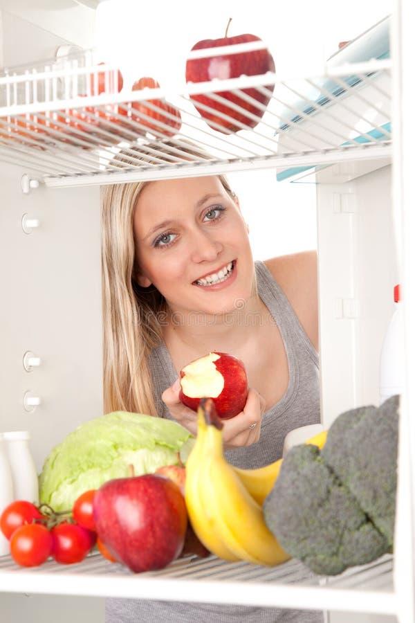 Alimento di sguardo teenager in frigorifero immagine stock