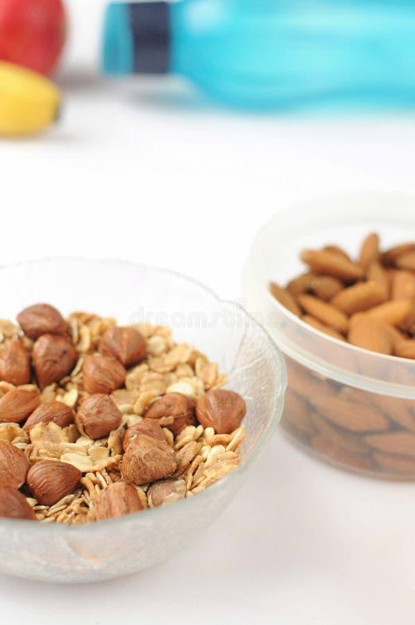 Alimento di uno stile di vita sano su fondo bianco Vista piana con lo spazio della copia Dadi, mandorle e farina d'avena Alimento fotografia stock