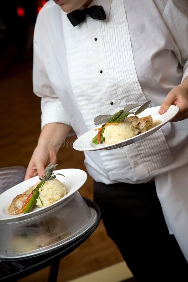 Alimento do casamento que está sendo serido por um empregado de mesa imagem de stock royalty free