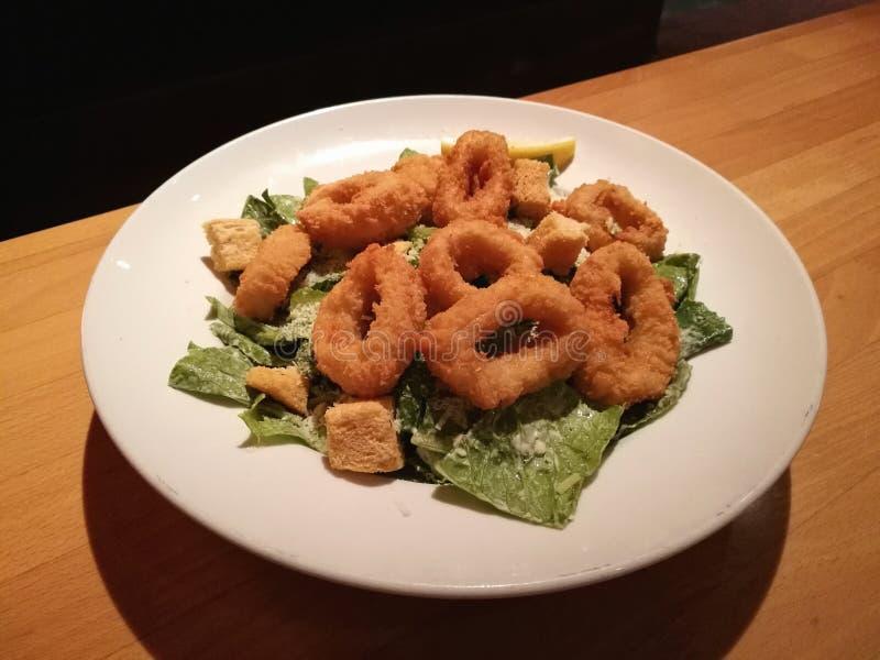 Alimento do estilista, calamari fritado no saque branco da placa com Caesar Salad na tabela de madeira com fundo da tabela do res imagens de stock