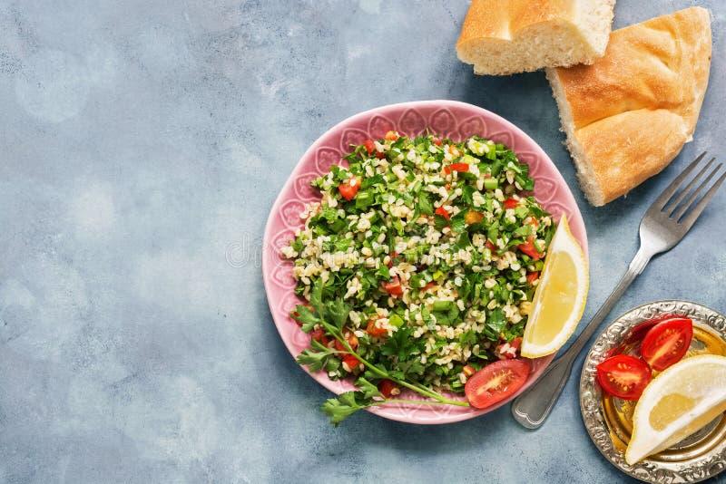 Alimento do Oriente Médio ou árabe em um fundo, em uma salada do taboulé e em um pão rústicos azuis do pão árabe Prato tradiciona foto de stock