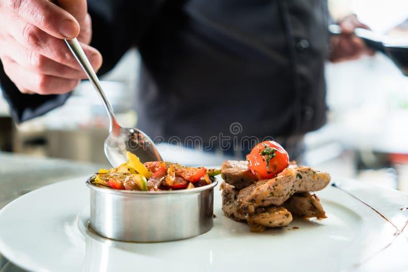 Alimento do revestimento do cozinheiro chefe na placa na cozinha do restaurante fotos de stock