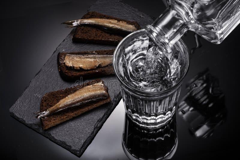 Alimento do russo Vidro da vodca, do filtro com vodca e do arenque pequeno com pão foto de stock