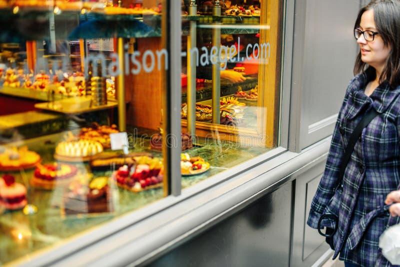 Alimento dolce francese pieno d'ammirazione della pasticceria della donna fotografie stock libere da diritti