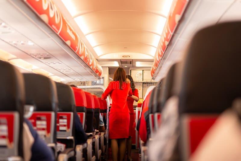 Alimento e bebidas do saque do aeromoço de Air Asia aos passageiros a bordo fotos de stock