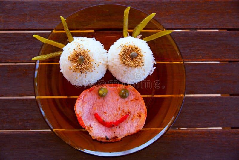 Alimento engraçado da criança com a cara do smiley do arroz e da carne fotografia de stock royalty free