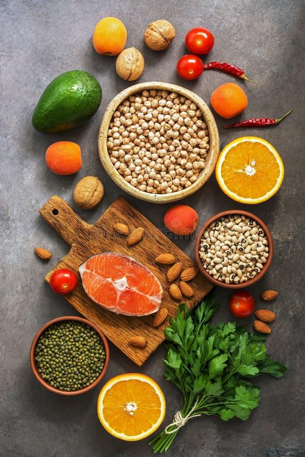 Alimento equilibrato sano, salmone, legumi, frutti, verdure, dadi, fondo rustico scuro Il concetto di cibo sano Disposizione pian fotografie stock