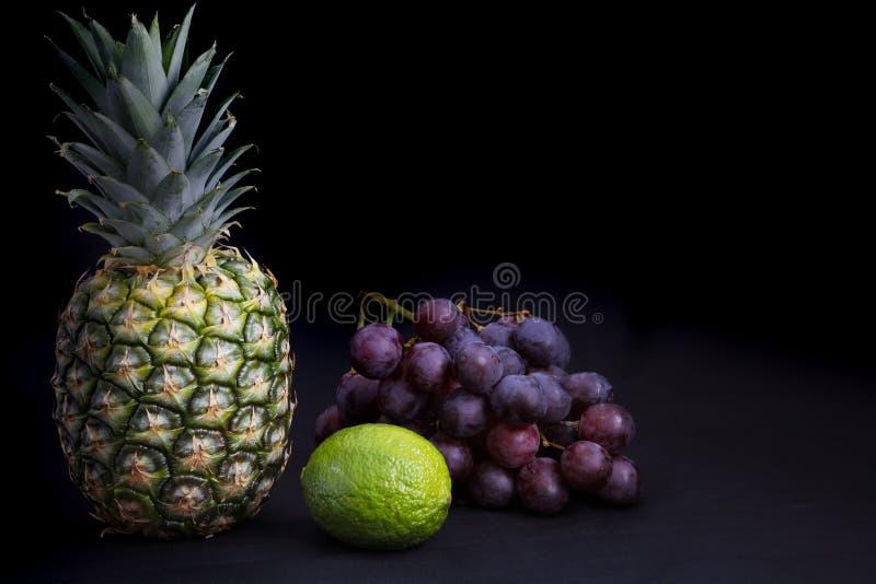 Alimento escuro - iluminação do claro-escuro no abacaxi, nas uvas e no cal imagens de stock