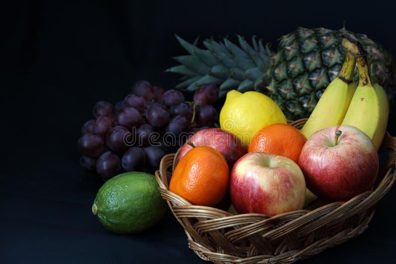 Alimento escuro - o claro-escuro misturou o fruto na cesta de vime foto de stock royalty free