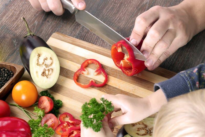 Alimento, família, cozimento e conceito dos povos - equipe o desbastamento da paprika na placa de corte com a faca na cozinha com fotos de stock