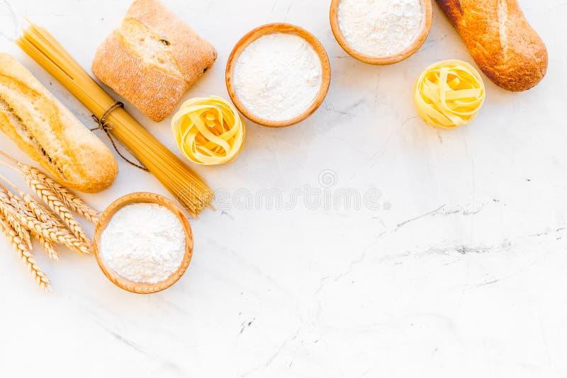 Alimento farinoso Pane fresco e pasta cruda vicino a farina in orecchie del grano e della ciotola sulla copia bianca di vista sup fotografie stock