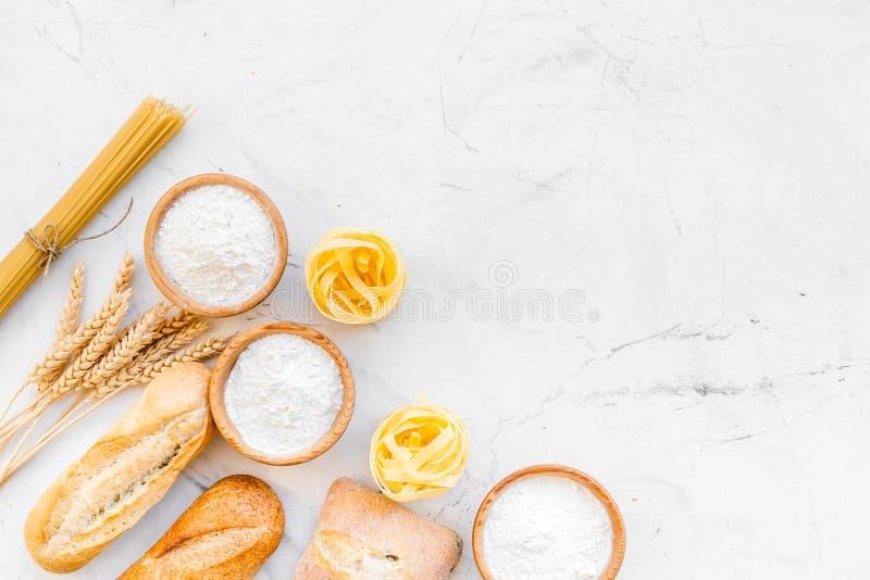 Alimento farinoso Pane fresco e pasta cruda vicino a farina in orecchie del grano e della ciotola sulla copia bianca di vista sup immagine stock