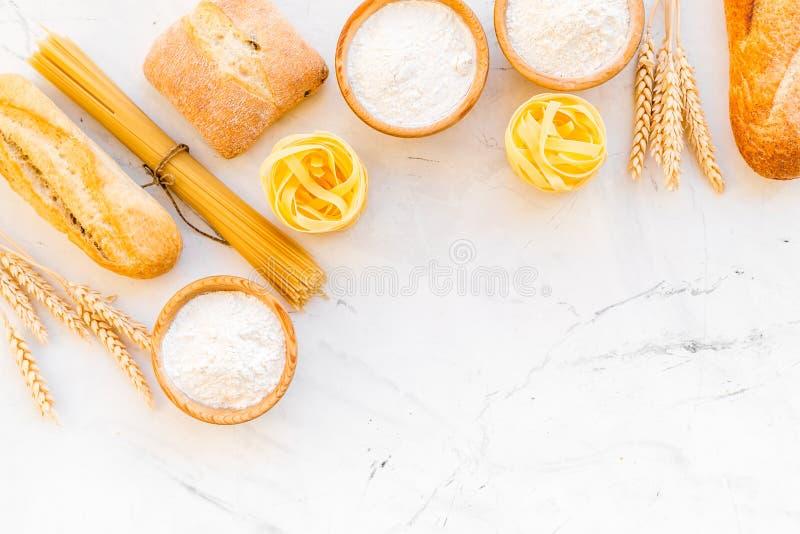 Alimento farinoso Pane fresco e pasta cruda vicino a farina in orecchie del grano e della ciotola sullo spazio bianco di vista su immagine stock libera da diritti