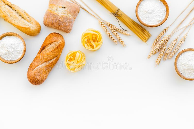 Alimento farinoso Pane fresco e pasta cruda vicino a farina in orecchie del grano e della ciotola sullo spazio bianco di vista su immagine stock