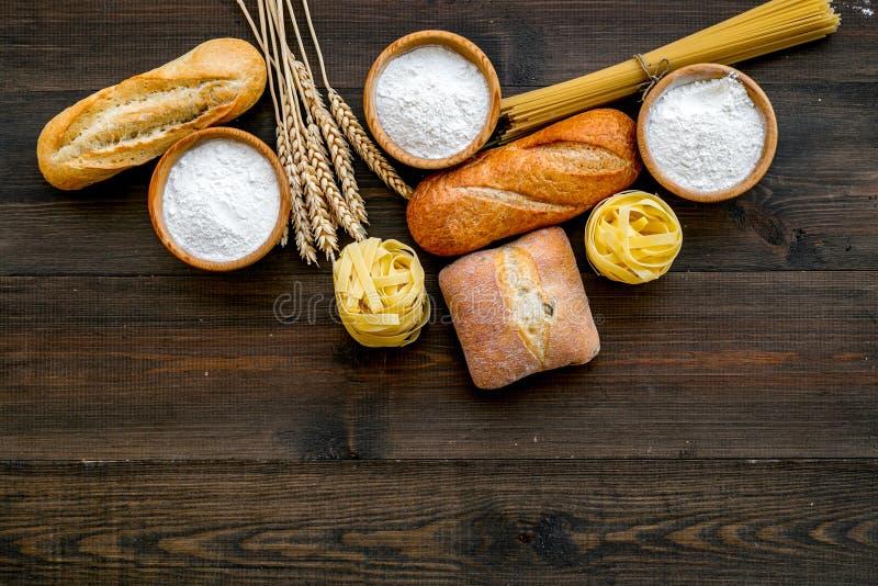 Alimento farinoso Pane fresco e pasta cruda vicino a farina in orecchie del grano e della ciotola sullo spazio di legno scuro di  fotografia stock libera da diritti