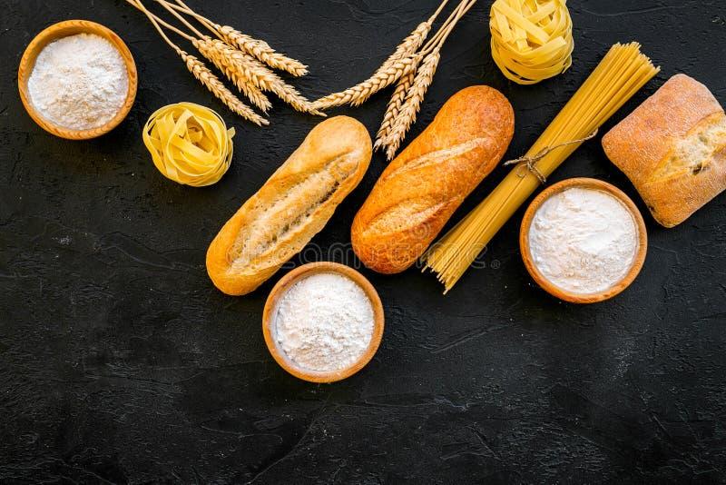 Alimento farinoso Pane fresco e pasta cruda vicino a farina in orecchie del grano e della ciotola sullo spazio nero di vista supe fotografia stock