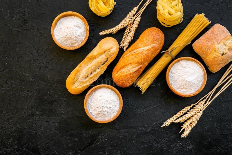 Alimento farinoso Pane fresco e pasta cruda vicino a farina in orecchie del grano e della ciotola sullo spazio nero di vista supe fotografie stock libere da diritti