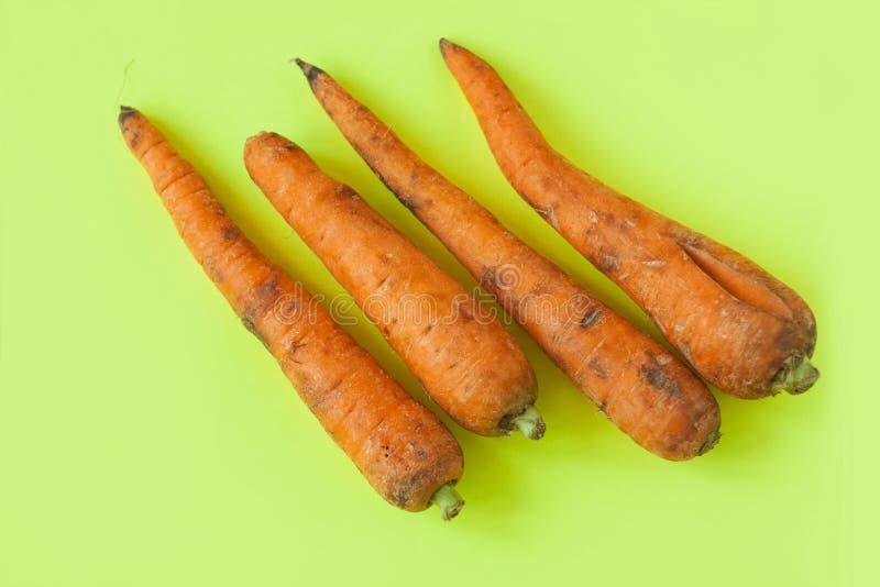 Alimento feio Cenouras orgânicas deformadas no fundo amarelo pastel Cores brilhantes, espa?o da c?pia fotografia de stock royalty free