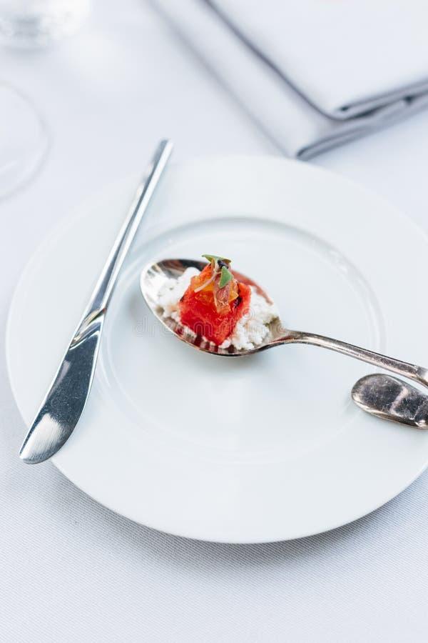 Alimento francês moderno: A melancia cortada com queijo branco do esmagamento serviu na colher de prata na placa branca com a cut imagem de stock