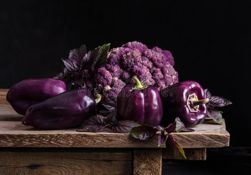 alimento fresco de vegetable Pimentas roxas escuras, couve-flor, folhas da manjericão imagens de stock