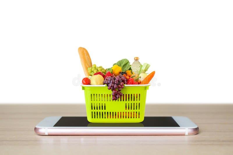 Alimento fresco e verdure in cestino della spesa verde sullo smartphone mobile sul piano d'appoggio di legno isolato su bianco immagine stock