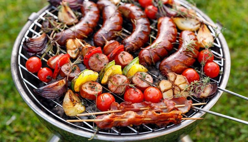 Alimento grelhado Vários produtos grelhados: Salsichas, espetos da carne e do vegetal, bacon e vegetais grelhados na placa da gra fotos de stock