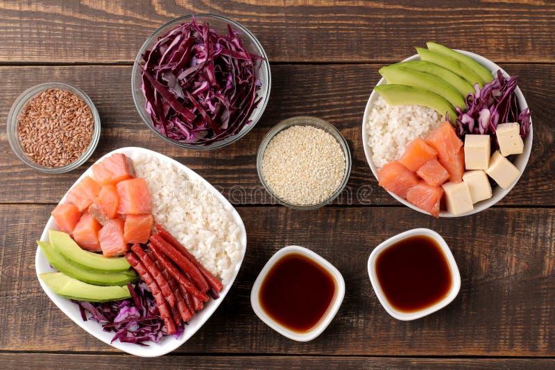 alimento havaiano da bacia do puxão uma placa do arroz, dos salmões, do abacate, da couve e do queijo, ao lado do molho do sésamo fotos de stock