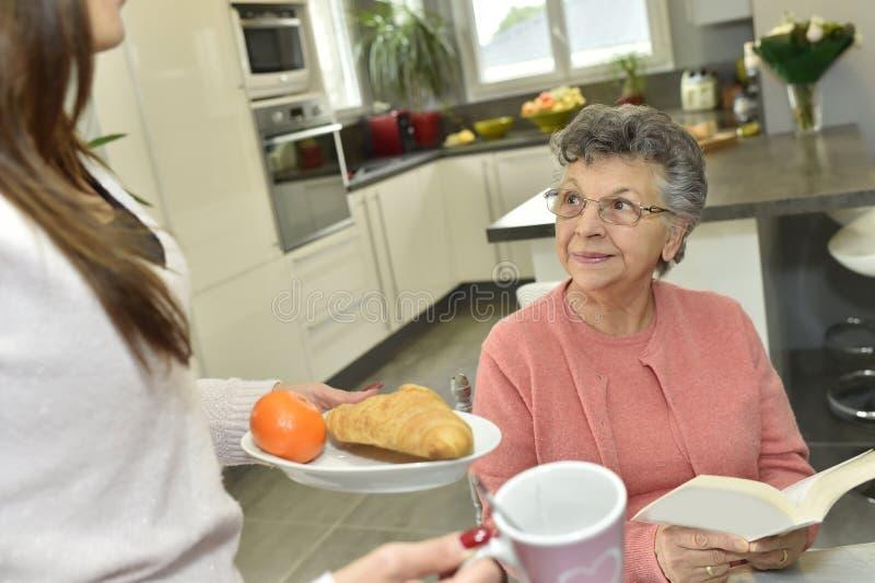 Alimento home do serviço da equipa de tratamento a uma mulher idosa fotografia de stock royalty free