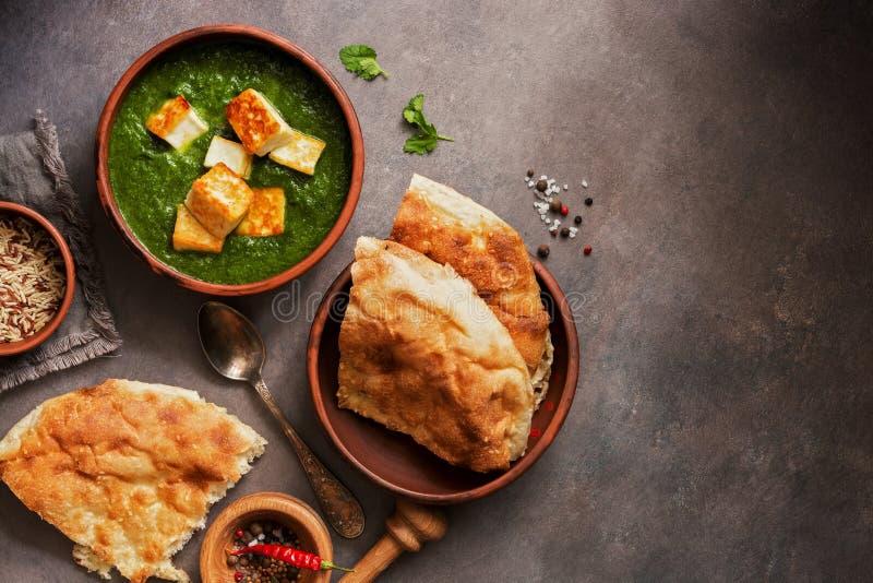 Alimento indiano di Palak Paneer, pane naan, riso e spezie su un fondo scuro Vista superiore, disposizione piana, spazio della co immagini stock libere da diritti